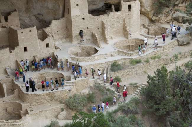 A group of tourists accompanied by a National Park Service guide tour the Cliff Palace ruins, Mesa Verde National Park, Colorado, USA