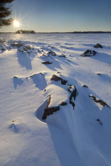 Sunrise on lake Kabetogama, viewing the snow-covered shoreline near Blue Fin Bay, Voyageurs National Park, Minnesota, USA