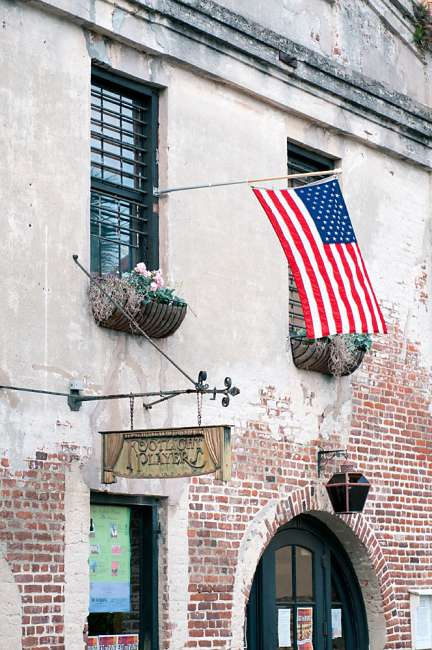 Charleston, South Carolina, USA.  An American flag waves in the breeze outside a historic Charleston building.